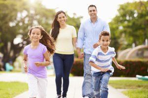 Hispanic Family Walking In Park Together Children Running Ahead Smiling