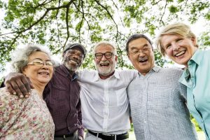 A diverse small group of adults aged 50 or older lean in together and smile