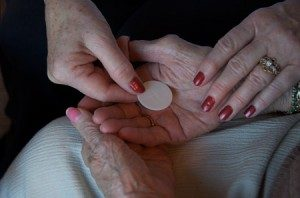 A more youthful hand places a Communion host in a more elderly hand